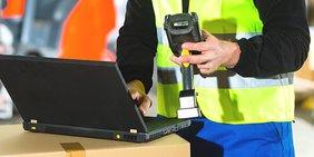 Mann mit Warnweste in Lager hält Scanner in der Hand und tippt auf Laptop